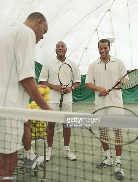 Three mature men laughing on tennis court