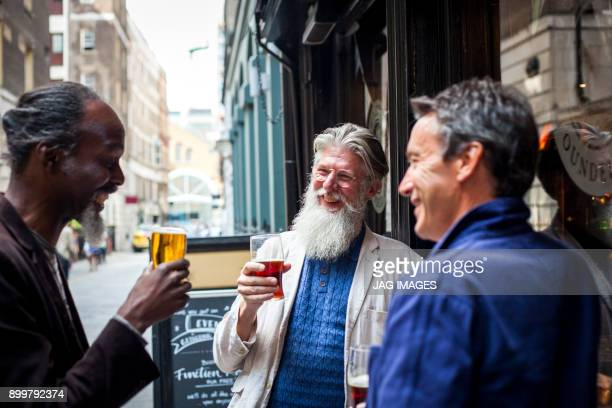 three mature men, standing outside pub, holding beer glasses, laughing - men friends beer outside stock pictures, royalty-free photos & images