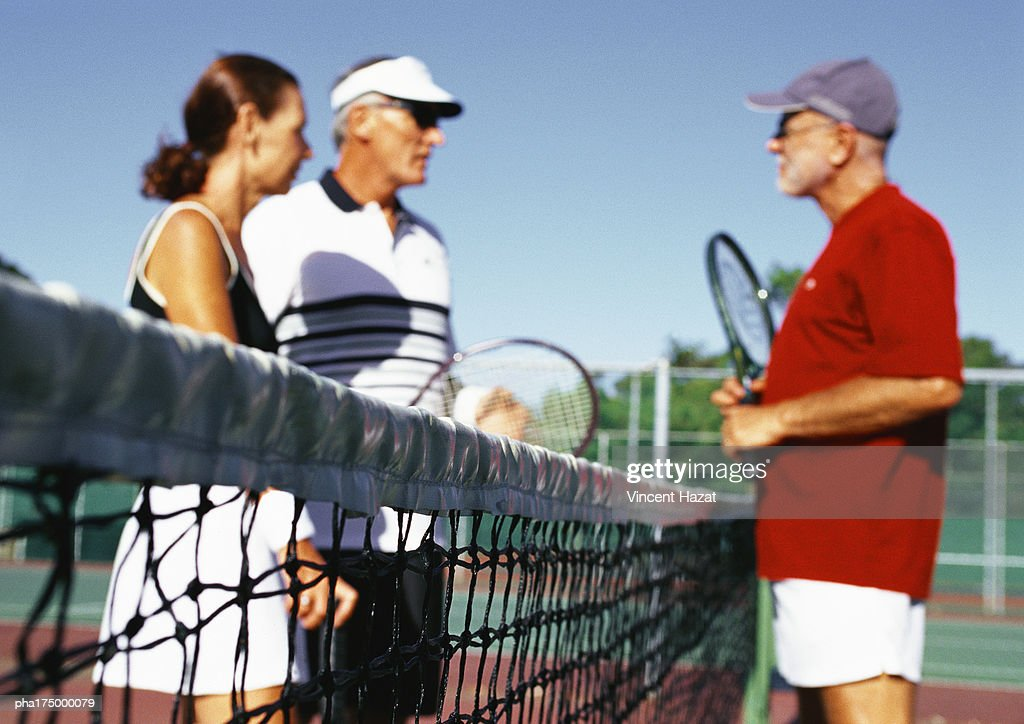 Three mature tennis players on court, side view : Stockfoto