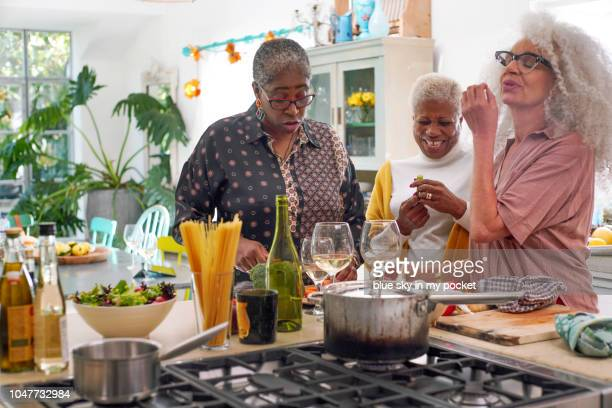 three mature woman in the kitchen preparing lunch - sólo con adultos fotografías e imágenes de stock
