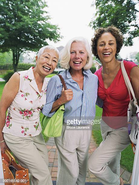 Three mature women at home entrance smiling