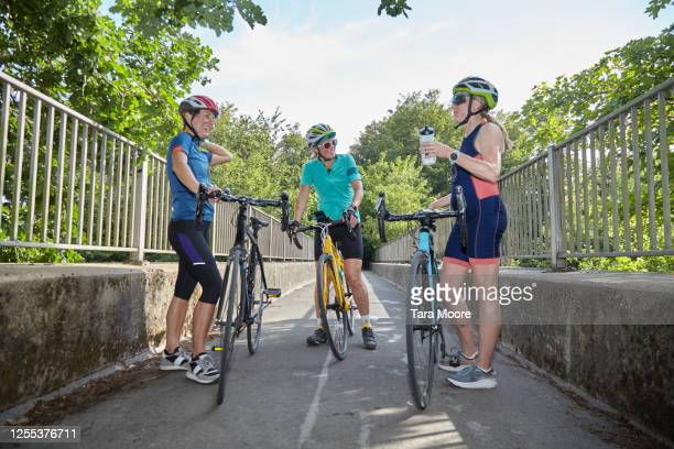 three mature women cyclists stopping for break - rural scene stock pictures, royalty-free photos & images