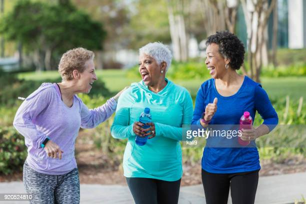 Three mature women exercising in park, walking, talking