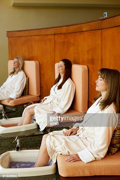 Three mature women getting pedicure in a beauty parlor
