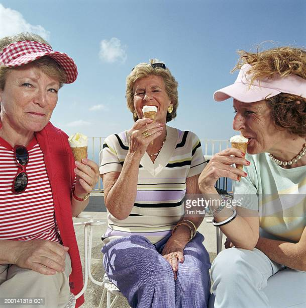 Three mature women holding icecreams, sitting outdoors, close up