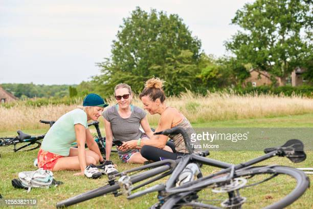 three mature women in park looking at mobile phone - social gathering stock pictures, royalty-free photos & images