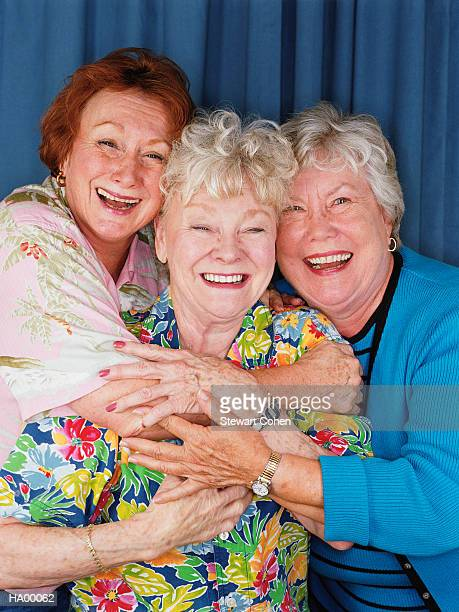Three mature women in photo booth embracing and laughing