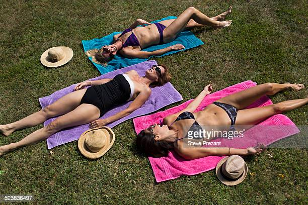 three mature women in swimwear, sunbathing on grass - women sunbathing stock photos and pictures