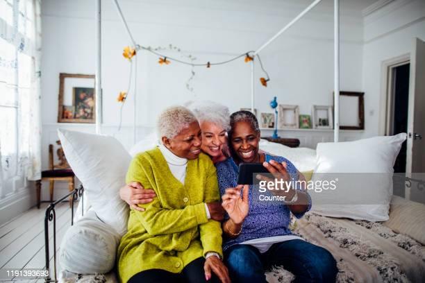 Three mature women looking at smart phone / London, UK.