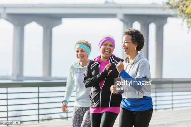 Three mature women power walking together on waterfront
