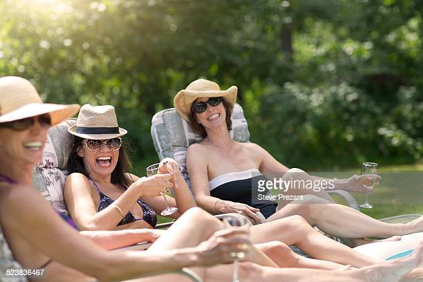 Three mature women relaxing in sun loungers, drinking wine