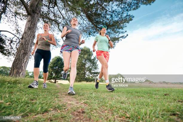 three mature women running in park - season 3 stock pictures, royalty-free photos & images
