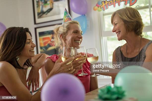 Three mature women toasting with wine glasses