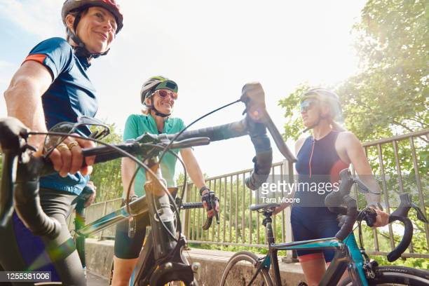 three mature women with racing bicycles - sports training stock pictures, royalty-free photos & images