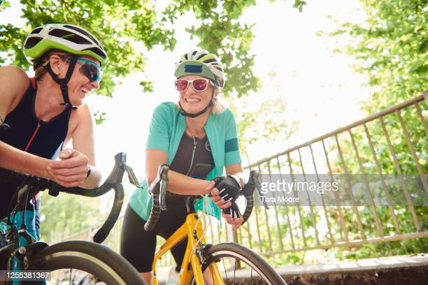 three mature women with racing bicycles - bicycle stock pictures, royalty-free photos & images