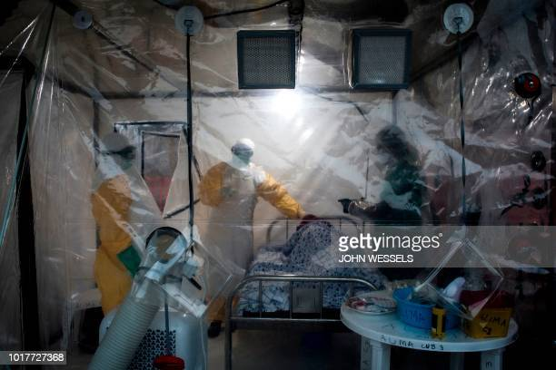 TOPSHOT Three medical workers check on an Ebola patient in a Biosecure Emergency care Unite on August 15 2018 in Beni The new ETC will hold ten...
