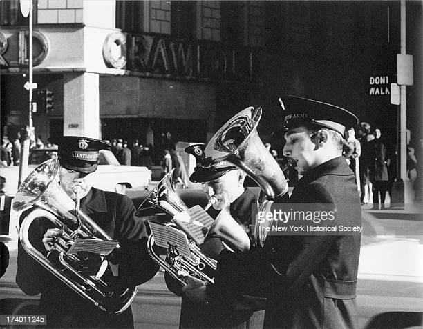 Three members of a Salvation Army band play on an unidentified street corner November 25 1961