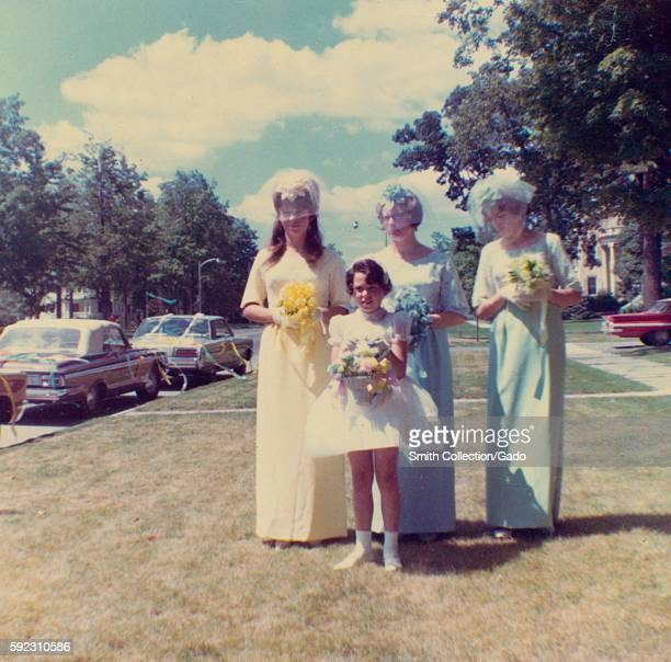 Three Members Of A Wedding Party Holding Colorful Bouquets And Posing Near Cars Decorated With Streamers