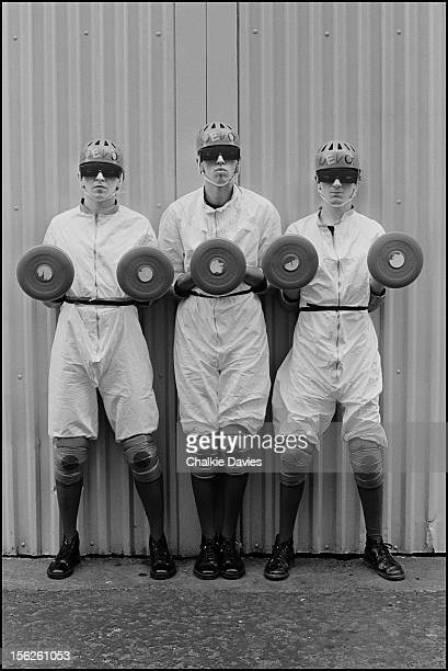 Three members of American alternative rock group Devo holding frisbees and wearing protective clothing London 1979