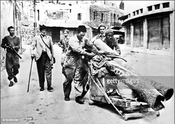 Three members of Haganah the Jewish Agency selfdefence force escort 12 May 1948 in Haifa three Palestinian Arabs expelled from the city after the...