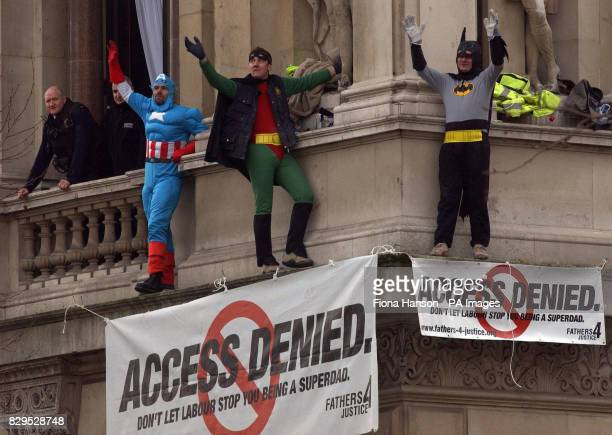 Three members of the Fathers 4 Justice dressed as superheroes Captain America, Batman and Robin on a ledge of the Foreign Office, above the junction...