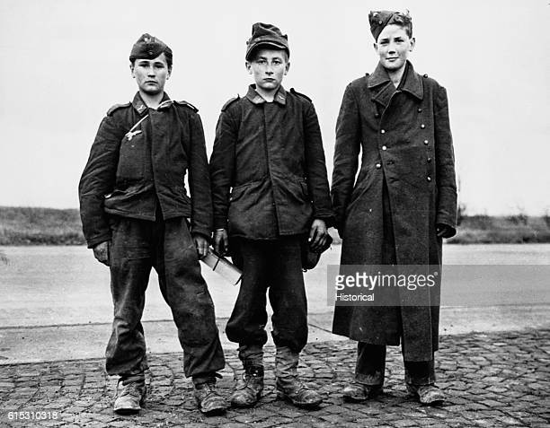 Three members of the Hitler Youth pose for a picture by the side of the road.
