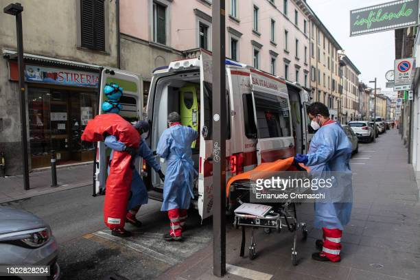 Three members of the Italian Red Cross pack an inflatable stretcher and other equipment on an ambulance on February 18, 2021 in Bergamo, Italy. The...
