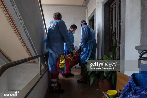 Three members of the Italian Red Cross, wearing PPE , lift an elderly woman lying on an inflatable stretcher up on the stairs of her home on February...