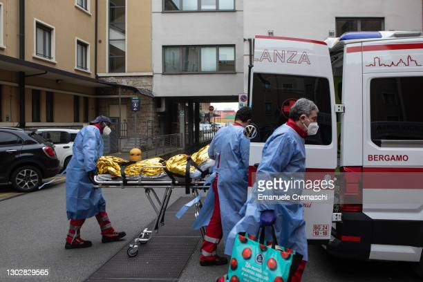 Three members of the Italian Red Cross, wearing PPE , transport an elderly woman at Humanitas Gavazzeni hospital on February 18, 2021 in Bergamo,...