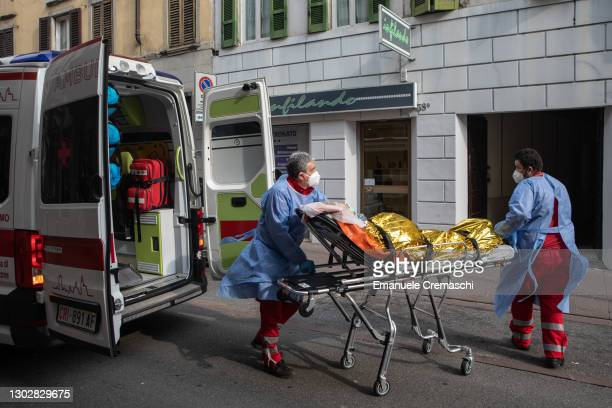 Three members of the Italian Red Cross, wearing PPE , transport an elderly woman on a stretcher outside her home on February 18, 2021 in Bergamo,...