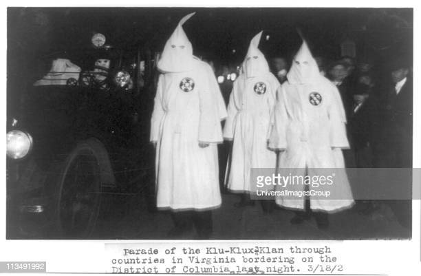 Three members of the Ku Klux Klan in masks and gowns taking part in a night parade To their left is a car carrying further masked members of the Klan...