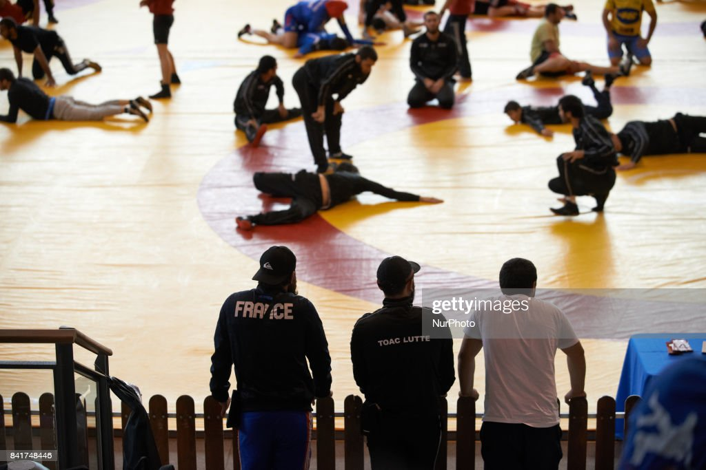 Three members of the TOAC Wrestling Club look at other members and competitors as they warm up. On 1st September 2017 in Clermond-Ferrand, France.