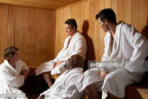 three men and woman talking in sauna - black woman in sauna stock pictures, royalty-free photos & images