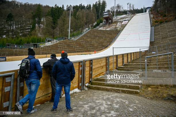 Three men are looking at the closed competition area of the mens FIS Ski Jumping World Cup after the approaching storm Sabine has forced the...