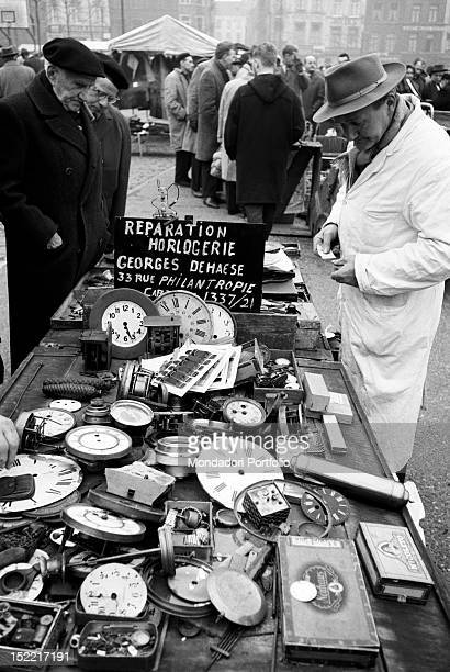 Three men are watching the goods on a stall of ancient watches in an antiques market Brussels 1962