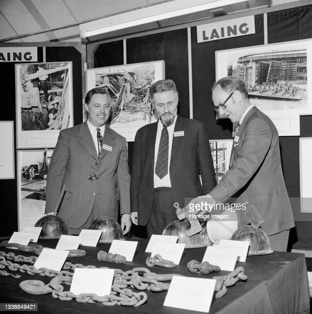 Three men at a Laing exhibition stand looking at a display of faulty lifting tackle and hard hats that had saved lives, during 'safety week' at the...