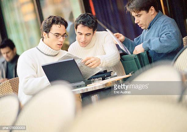 Three men at cafe terrace, looking at documents