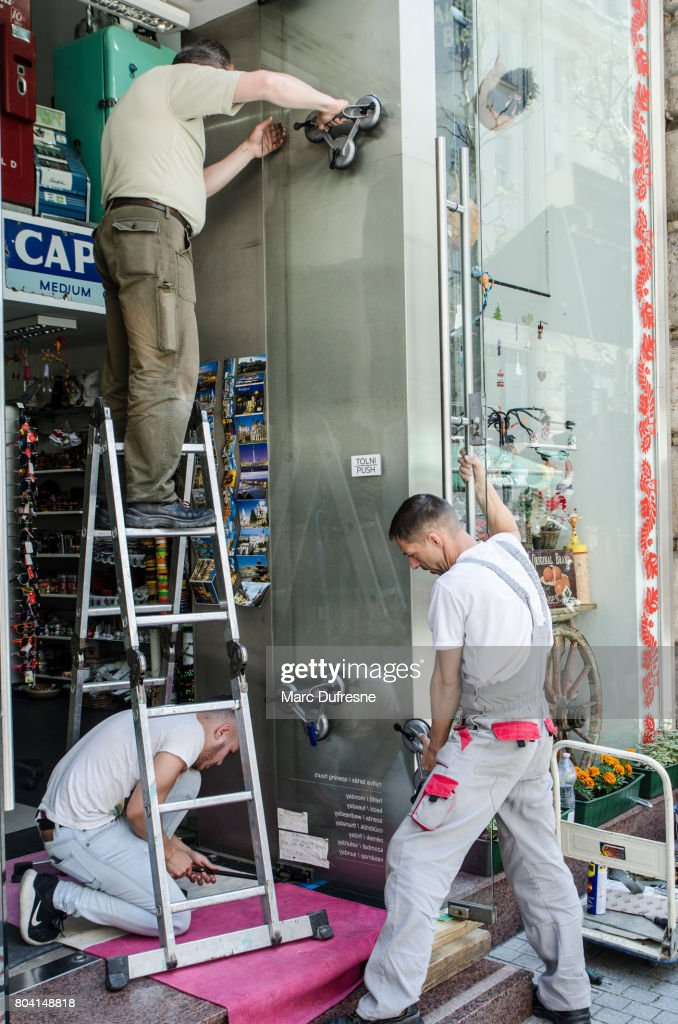 Three Men Changing The Glass Door Of A Retail Store In Budapest