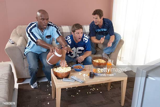 Three men cheering watching football in living room