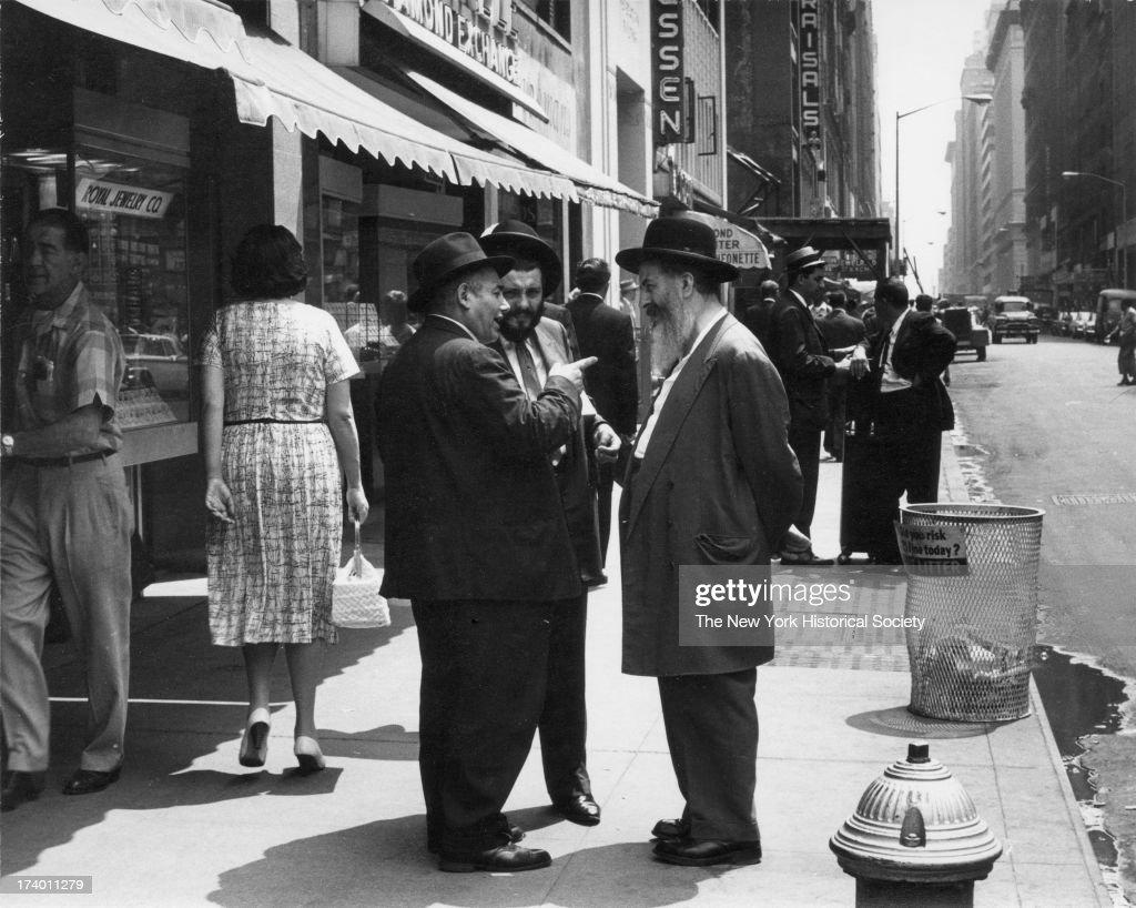 Three Men Conversing On A Sidewalk In The Diamond District : News Photo
