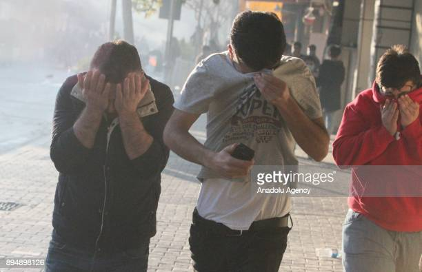Three men cover their faces from the tear gas smoke while demonstrators clash with riot police within antigovernment protests in Sulaymaniyah Iraq on...
