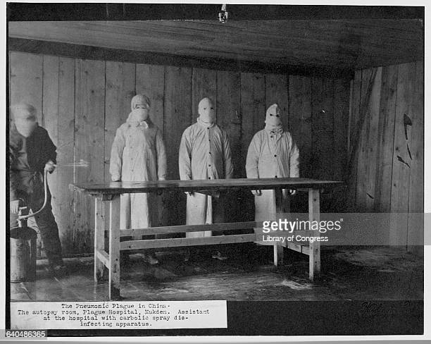 Three men covered from head to toe with protective clothing watch as a Hospital assistant uses a carbolic spray to disinfect the autopsy table at the...