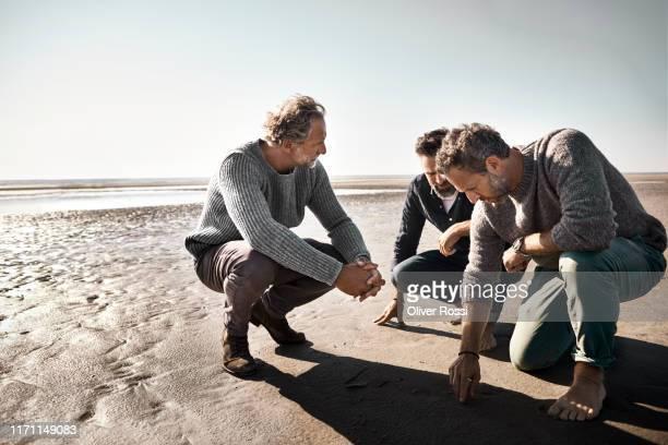 three men crouching on the beach drawing into sand - drei personen stock-fotos und bilder