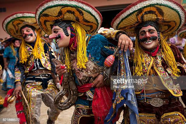 Three men dance with snake in Guatemalan festival