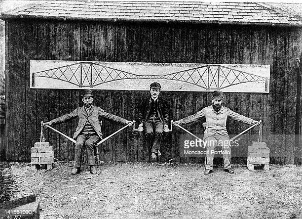 Three men demonstrating Forth Bridge stability The embossed railway bridge was designed by English engineer Benjamin Baker Edinburgh 1890s