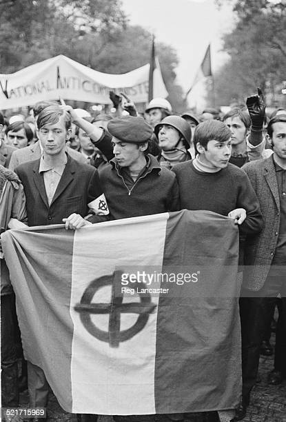 Three men display a flag on an anticommunism march during civil unrest in Paris 30th May 1968