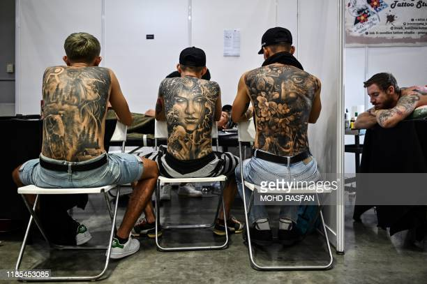 Three men display their tattoos while tattoo artist works on clients during the International Malaysia Tattoo Expo in Kuala Lumpur on November 29...