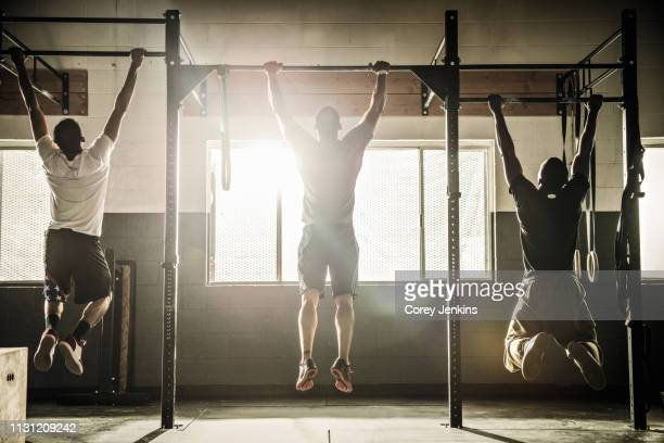 three men doing pull ups on exercise bar in gymnasium - chin ups stock photos and pictures