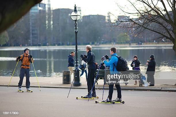 CONTENT] Three men dressed in winter sports clothing skiing using small customised skateboards to travel through Hyde Park London England Two of them...