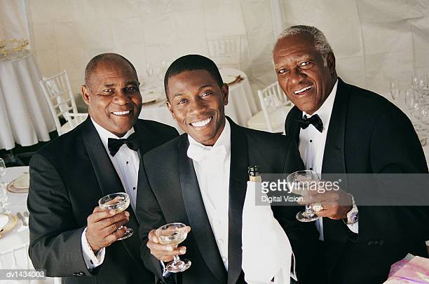 Three Men Drink a Toast Indoors at a Wedding Reception